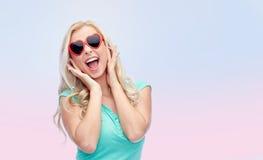 Mujer joven feliz en gafas de sol de la forma del corazón Fotos de archivo libres de regalías