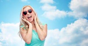 Mujer joven feliz en gafas de sol de la forma del corazón Imágenes de archivo libres de regalías