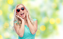 Mujer joven feliz en gafas de sol de la forma del corazón Foto de archivo libre de regalías