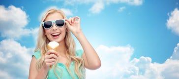 Mujer joven feliz en gafas de sol que come el helado Imagen de archivo libre de regalías