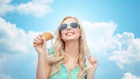 Mujer joven feliz en gafas de sol que come el helado Fotografía de archivo