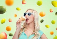Mujer joven feliz en gafas de sol que come el helado Foto de archivo libre de regalías