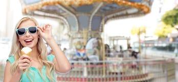Mujer joven feliz en gafas de sol que come el helado Foto de archivo