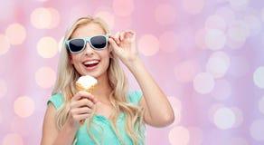 Mujer joven feliz en gafas de sol que come el helado Imagenes de archivo