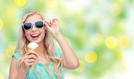 Mujer joven feliz en gafas de sol que come el helado Imágenes de archivo libres de regalías