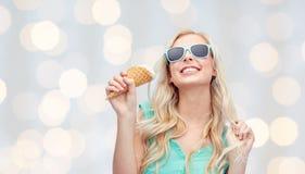 Mujer joven feliz en gafas de sol que come el helado Fotografía de archivo libre de regalías