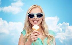 Mujer joven feliz en gafas de sol que come el helado Fotos de archivo