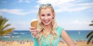 Mujer joven feliz en gafas de sol que come el helado Imagen de archivo