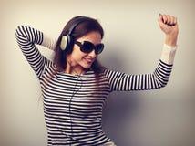 Mujer joven feliz en gafas de sol que escucha la música del headpho Imagen de archivo libre de regalías