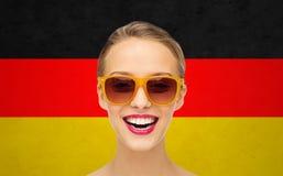 Mujer joven feliz en gafas de sol sobre bandera alemana Fotografía de archivo