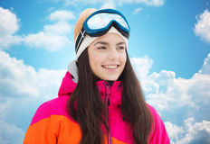 Mujer joven feliz en gafas del esquí sobre el cielo azul Foto de archivo libre de regalías