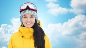 Mujer joven feliz en gafas del esquí sobre el cielo azul Imagenes de archivo
