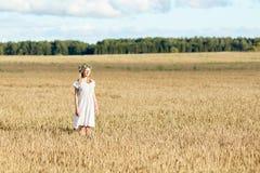 Mujer joven feliz en guirnalda de la flor en campo de cereal Foto de archivo