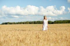 Mujer joven feliz en guirnalda de la flor en campo de cereal Fotos de archivo libres de regalías