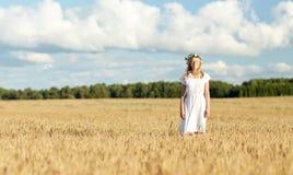 Mujer joven feliz en guirnalda de la flor en campo de cereal Fotos de archivo