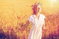 Mujer joven feliz en guirnalda de la flor en campo de cereal Fotografía de archivo libre de regalías