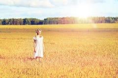 Mujer joven feliz en guirnalda de la flor en campo de cereal Imagen de archivo