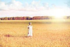 Mujer joven feliz en guirnalda de la flor en campo de cereal Imagenes de archivo