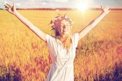 Mujer joven feliz en guirnalda de la flor en campo de cereal Foto de archivo libre de regalías