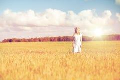 Mujer joven feliz en guirnalda de la flor en campo de cereal Imagen de archivo libre de regalías