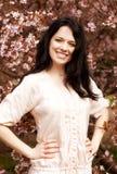 Mujer joven feliz en jardín de flores de la primavera Fotografía de archivo