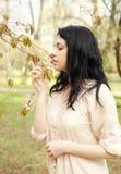 Mujer joven feliz en jardín de flores de la primavera Fotos de archivo