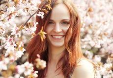 Mujer joven feliz en jardín de flores de la primavera Imagenes de archivo