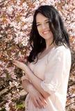 Mujer joven feliz en jardín de flores de la primavera Imágenes de archivo libres de regalías