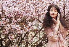 Mujer joven feliz en jardín de flores de la primavera Foto de archivo libre de regalías