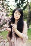 Mujer joven feliz en jardín de flores de la primavera Imagen de archivo