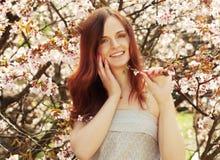 Mujer joven feliz en jardín de flores de la primavera Fotografía de archivo libre de regalías