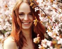 Mujer joven feliz en jardín de flores de la primavera Foto de archivo