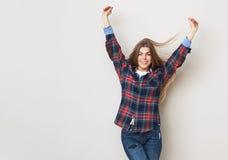 Mujer joven feliz en la camisa de tela escocesa que presenta contra la pared Imagen de archivo