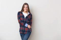 Mujer joven feliz en la camisa de tela escocesa que presenta contra la pared Foto de archivo libre de regalías