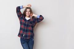 Mujer joven feliz en la camisa de tela escocesa que presenta contra la pared Fotografía de archivo
