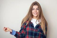 Mujer joven feliz en la camisa de tela escocesa que presenta contra la pared Imágenes de archivo libres de regalías