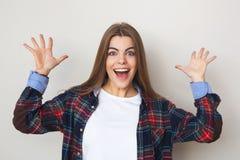 Mujer joven feliz en la camisa de tela escocesa que presenta contra la pared Foto de archivo