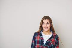 Mujer joven feliz en la camisa de tela escocesa que presenta contra la pared Fotos de archivo libres de regalías