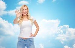 Mujer joven feliz en la camiseta blanca que muestra la muestra aceptable Foto de archivo