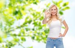 Mujer joven feliz en la camiseta blanca que muestra la muestra aceptable Fotos de archivo