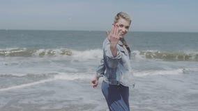 Mujer joven feliz en la chaqueta del dril de algodón que tiene tiempo de la diversión en la playa sola