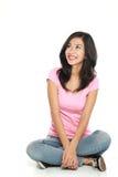 Mujer joven feliz en la sentada y el pensamiento de la ropa de sport Imagenes de archivo