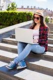 mujer joven feliz en las gafas de sol que se sientan en las escaleras de la ciudad y que usan el ordenador portátil Fotografía de archivo