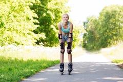 Mujer joven feliz en los rollerblades que montan al aire libre Imagenes de archivo