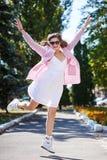 Mujer joven feliz en los vidrios que saltan en el parque con alegría Foto de archivo