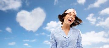 Mujer joven feliz en m?scara el dormir del pijama y del ojo imagenes de archivo