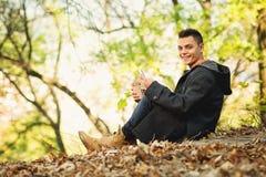 Mujer joven feliz en otoño en parque con el teléfono elegante y el café para llevar Imagenes de archivo