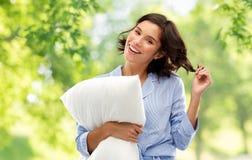 Mujer joven feliz en pijama con la almohada fotografía de archivo libre de regalías