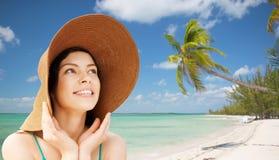 Mujer joven feliz en sombrero de paja en la playa tropical Fotografía de archivo libre de regalías