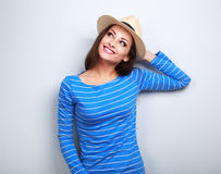 Mujer joven feliz en sombrero de paja que piensa y que mira para arriba en b azul Fotos de archivo libres de regalías